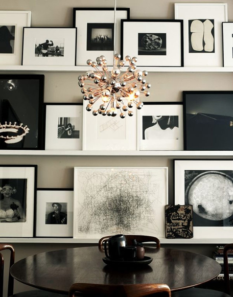 Instead of hanging the wall art on the wall, create ledges, to allow for regular changes to your collage. In this case, a black and white themed wall art collage creates a sleek and retro feel.